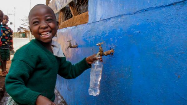 Schulkind-entnimmt-sauberes-Wasser-aus-Grossfilter